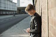 Young man wearing earbuds looking at cell phone - UUF005933