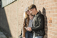 Relaxed young couple with cell phone and earbuds outdoors - UUF005936