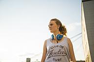 Teenage girl wearing headphones looking around - UUF005957