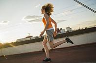 Teenage girl running on a bridge - UUF005966