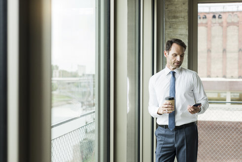 Portrait of businessman with coffee to go looking at his smartphone - UUF005967