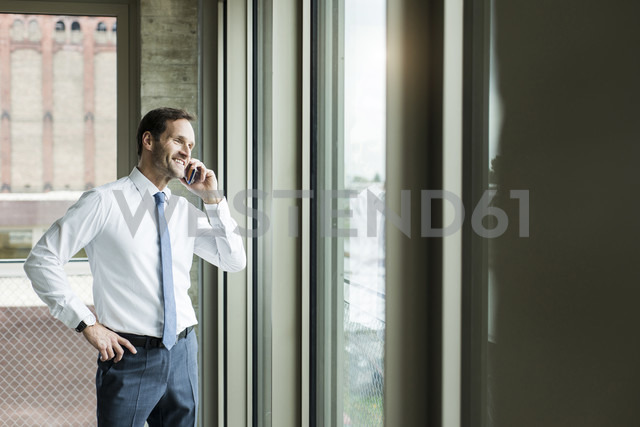 Portrait of businessman telephoning smartphone - UUF005970