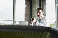 Portrait of pensive businessman at his desk in the office - UUF005982
