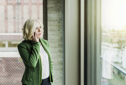 Portrait of blond businesswoman telephoning with smartphone - UUF005985