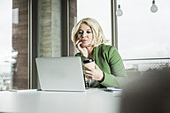 Portrait of thinking businesswoman with coffee to go looking at her laptop in the office - UUF006000