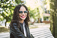 Portrait of smiling woman wearing sunglasses and leather jacket sitting on a park bench - RAEF000642