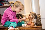 Little girl applying make up on her doll - JFEF000748