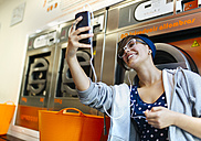Young woman taking a selfie with smartphone in a launderette - MGOF001030