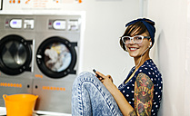 Portrait of tattooed young woman hearing music with earphones in a launderette - MGOF001036