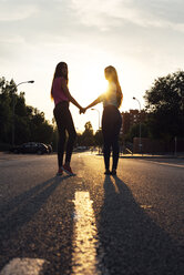 Two female friends standing hand in hand at backlight - GEMF000476