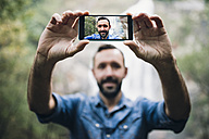 Bearded man taking a selfie with smartphone in front of a waterfall - RAEF000651