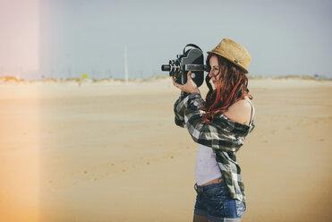 Spain, El Puerto de Santa Maria, young woman using old film camera on the beach - KIJF000031