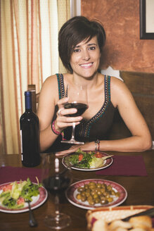 Smiling woman with red wine and dishes in a restaurant - JASF000242