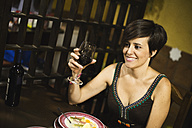 Smiling woman holding red wine glass in a restaurant - JASF000245