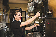 Waitress tapping beer in pub - JASF000251
