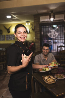 Portrait of smiling waitress serving wine and dishes - JASF000257