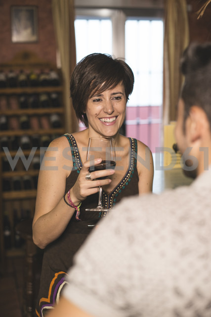 Smiling couple at bar drinking red wine - JASF000260