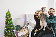 Laughing couple with their cat at home - EBSF001034
