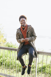 Portrait of smiling young man with smartphone sitting on a railing - EBSF001040