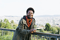 Spain, Barcelona, portrait of smiling young man with smartphone leaning on railing - EBSF001046