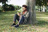 Young man with smartphone leaning against tree trunk on a meadow - EBSF001055