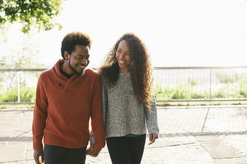Portrait of happy young couple walking hand in hand - EBSF001070
