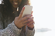 Hands of young woman holding smartphone - EBSF001076
