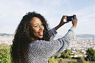 Spain, Barcelona, portrait of young woman taking a picture of view with her smartphone - EBSF001079