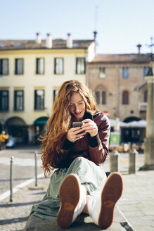 Italy, Padua, woman sitting outdoors at town square with cell phone - GIOF000488