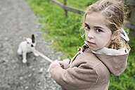 Portrait of little girl with her French bulldog in the background - RAEF000656