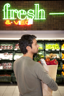 Man with paper bag of vegetables in a supermarket - RMAF000220