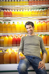 Portrait of smiling man sitting in front of fridge with rows of juice bottles in a supermarket - RMAF000223