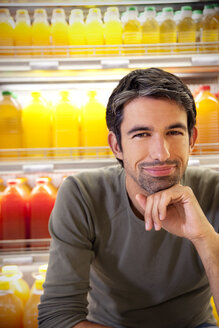 Portrait of smiling man sitting in front of fridge with rows of juice bottles in a supermarket - RMAF000226