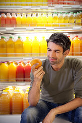 Portrait of smiling man sitting in front of fridge with rows of juice bottles in a supermarket holding an orange - RMAF000229