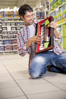Portrait of happy man crouching on the floor of a supermarket playing with toy keyboard - RMAF000232