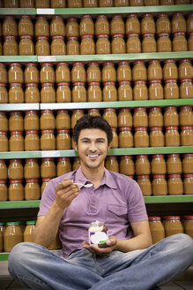 Smiling man sitting on the floor of a supermarket tasting glass of chocolate spread - RMAF000244