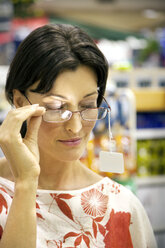 Woman in a shop trying spectacles on - RMAF000250