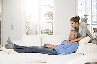 Couple relaxing on couch at home using laptop - FKF001531