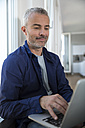 Mature man working from home using laptop - FKF001543