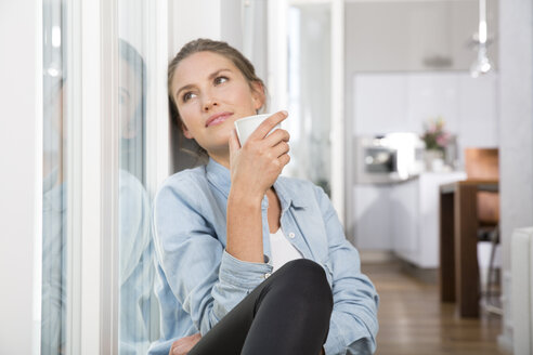 Young woman sitting at the window, drinking coffee - FKF001552