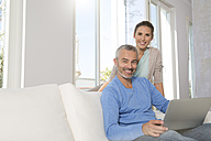 Couple relaxing on couch at home using laptop - FKF001567