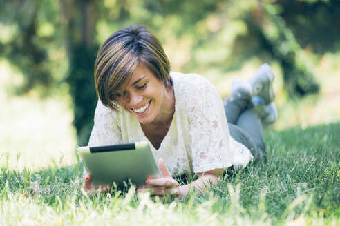 Teenage girl lying in grass looking at digital tablet - GIOF000519