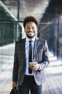 Portrait of confident young businessman with cell phone outdoors - EBSF001113