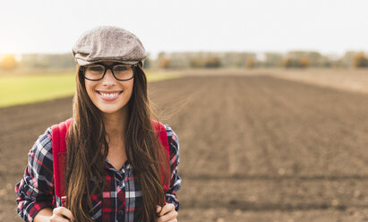 Portrait of smiling young woman with backpack in the countryside - UUF006036