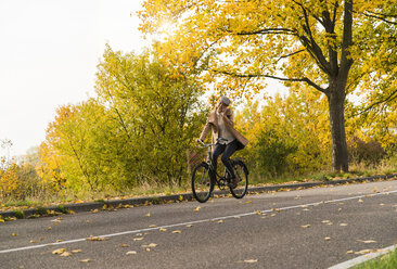 Young woman on cell phone riding bicycle in autumn landscape - UUF006048