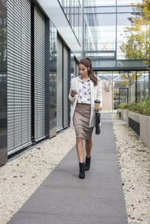 Young businesswoman outdoors walking and looking at cell phone - UUF006054