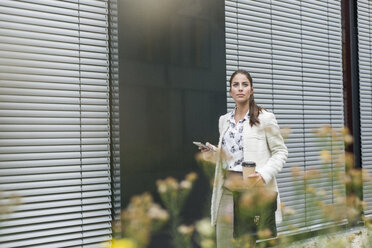 Young businesswoman outdoors holding cell phone and coffee to go - UUF006060