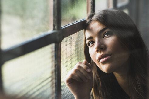 Brunette woman looking out of window - UUF006096