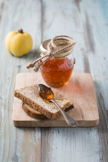 Quince jelly, slice of bread on chopping board - MYF001218