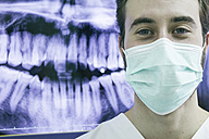 Dentist wearing a mask with an x-ray of teeth in background - ABZF000152